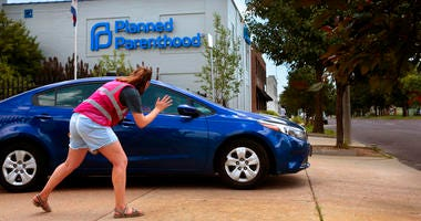 Ashlyn Myers of the Coalition for Life St. Louis waves to a Planned Parenthood staff member.