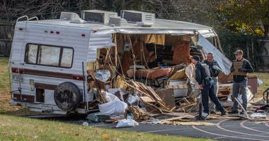 Police examine a stolen RV after ramming it multiple times with an armored vehicle while searching for a Marine deserter who is wanted for questioning in a murder case, in Roanoke, Va.