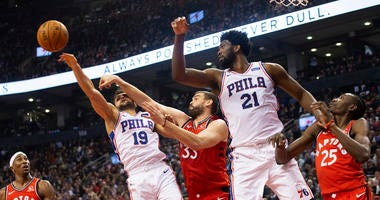 Philadelphia 76ers guard Raul Neto (19) jumps for a rebound ahead of Toronto Raptors' Marc Gasol (33) as 76ers' Joel Embiid (21) and Raptors' Chris Boucher (25) and Rondae Hollis-Jefferson (4) look on during the first half of an NBA basketball game.