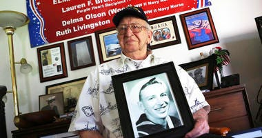 In this Nov. 17, 2016, file photo, Lauren Bruner, a survivor of the USS Arizona which was attacked on Dec. 7, 1941, holds with a 1940 photo of himself at his home in La Mirada, Calif.