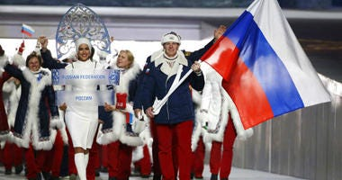 Alexander Zubkov of Russia carries the national flag.