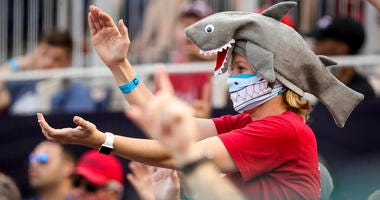 A fan wears a shark hat as Washington Nationals' Gerardo Parra comes up to bat in the eighth inning of a baseball game against the Cleveland Indians at Nationals Park in Washington on Sept. 29, 2019.