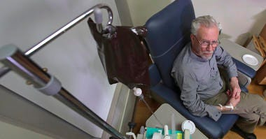 In this Nov. 22, 2019, photo, Charles Flagg, who is stricken with Alzheimer's disease, receives the contents of an intravenous bag while participating in a study on the drug Aducanumab at Butler Hospital in Providence, R.I.