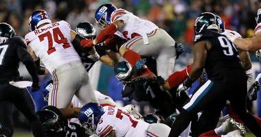 New York Giants' Saquon Barkley (26) leaps over Philadelphia Eagles' Daeshon Hall (74) during the first half of an NFL football game, Monday, Dec. 9, 2019, in Philadelphia.