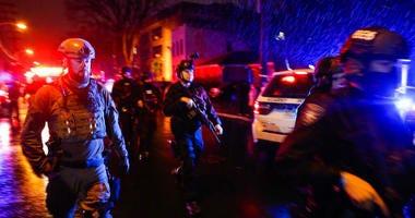 Law enforcement personnel walk near the scene following a shooting.