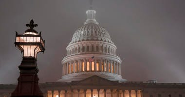 The U.S. Capitol in Washington is shrouded in mist, Friday night, Dec. 13, 2019.