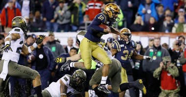 Navy's Malcolm Perry leaps over Army's Donavan Lynch during the second half of the Army-Navy Game.