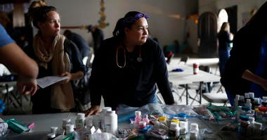 In this Dec. 14, 2019, photo, Psyche Calderon, center, pauses for a moment as she works alongside other volunteer health care professionals in a shelter for migrants in Tijuana, Mexico.