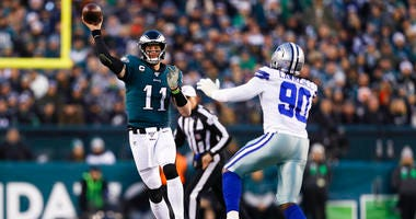 Philadelphia Eagles quarterback Carson Wentz (11) throws a pass as Dallas Cowboys defensive end Demarcus Lawrence defends during the first half of an NFL football game.
