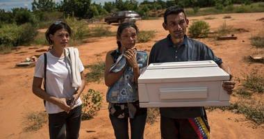 Roberto Parra carries the remains of his son Matias Alejandro alongside his wife Maria Isabel Parra and daughter Alejandra Parra at San Sebastian municipality cemetery before burying him in Maracaibo, Venezuela, Nov. 27, 2019.