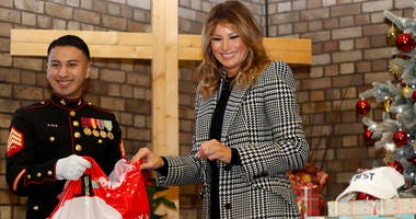 First lady Melania Trump joins local students and U.S. Marines stationed at the U.S. Embassy, wrapping holiday presents to be donated to the Salvation Army, at the Salvation Army Clapton Center in London.