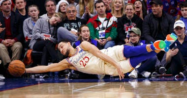 Philadelphia 76ers' Ben Simmons dives as he tries to save the ball from going out of bounds during the first half of an NBA basketball game against the Milwaukee Bucks.