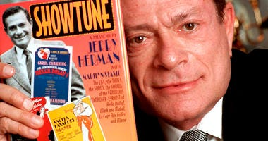"In this Nov. 19, 1996, file photo, composer Jerry Herman displays his book ""Showtune,"" in New York. Herman, the Tony Award-winning composer behind ""Hello, Dolly!"" and ""La Cage aux Folles,"" has died at age 88."