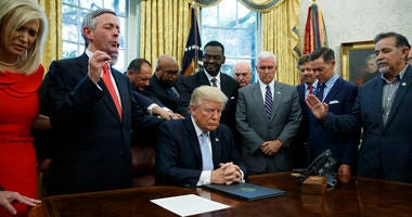 religious leaders pray with President Donald Trump after he signed a proclamation for a national day of prayer to occur on Sunday, Sept. 3, 2017, in the Oval Office of the White House in Washington.