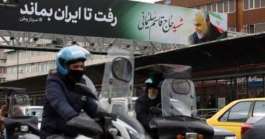 Vehicles drive past a billboard showing a portrait of Iranian Revolutionary Guard Gen. Qassem Soleimani, who was killed in a U.S. airstrike in Iraq, in Tehran, Iran, Saturday.