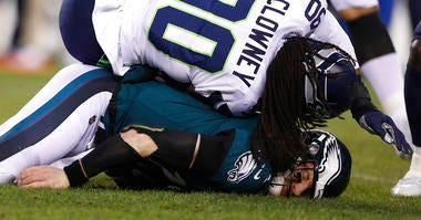 Philadelphia Eagles' Carson Wentz (11) is hit by Seattle Seahawks' Jadeveon Clowney (90) during the first half of an NFL wild-card playoff football game, Sunday, Jan. 5, 2020, in Philadelphia.