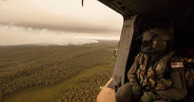 In this Sunday, Jan. 5, 2020, photo provided by Australian Department of Defence, a Royal Australian Navy MRH-90 helicopter crew member looks out over fires burning near Cann River, Australia.