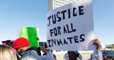 Prisoner advocates hold signs supporting inmate rights at a protest outside the Capitol in Jackson, Miss., Tuesday, Jan. 7, 2020.