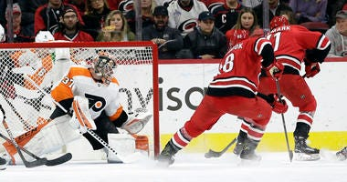 Carolina Hurricanes center Lucas Wallmark, right, of Sweden, scores against Philadelphia Flyers goaltender Brian Elliott (37) during the first period of an NHL hockey game in Raleigh, N.C., Tuesday, Jan. 7, 2020.
