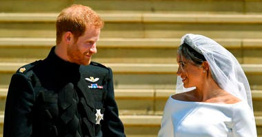 Britain's Prince Harry and Meghan Markle walk down the steps after their wedding at St. George's Chapel in Windsor Castle in Windsor, England.