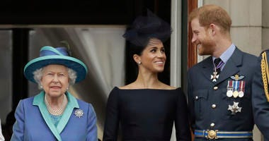 Britain's Queen Elizabeth II, and Meghan the Duchess of Sussex and Prince Harry watch a flypast of Royal Air Force aircraft pass over Buckingham Palace in London.