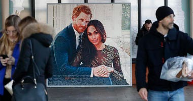 People walk past a picture of Britain's Prince Harry and Meghan Duchess of Sussex, in Windsor, Friday.