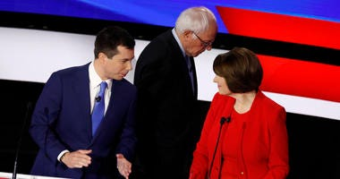 Democratic presidential candidates former South Bend Mayor Pete Buttigieg, left, and Sen. Amy Klobuchar, D-Minn., talk while Sen. Bernie Sanders, I-Vt., heads off stage at a break Tuesday, Jan. 14, 2020