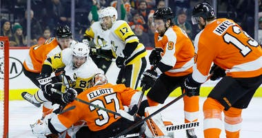 Pittsburgh Penguins' Sidney Crosby (87) tries to get a shot past Philadelphia Flyers' Brian Elliott (37) as Philippe Myers (5), Ivan Provorov (9) and Kevin Hayes (13) defend during the third period of an NHL hockey game, Tuesday, Jan. 21, 2020.