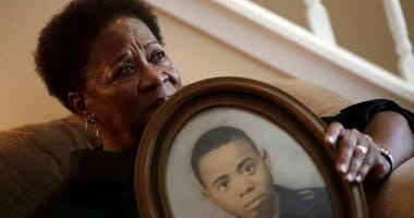 In this Aug. 9, 2018 photo, Eberlene King poses with a photograph of her brother William Roy Prather when he was about 15-years-old at her home in Doraville, Ga.