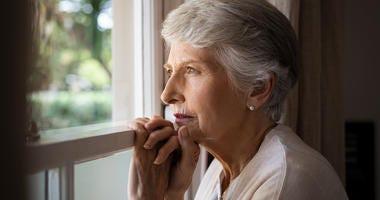 Senior citizen looking through window