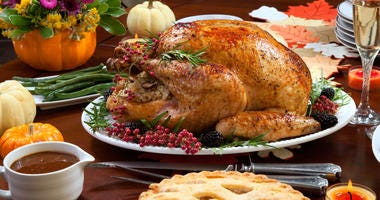 Roasted pepper turkey for Thanksgiving, garnished with pink pepper, blackberry, and fresh rosemary twigs on a dinner table decorated with mini pumpkins, beans, carrots, baked potato, pie, cranberry relish, gravy, flowers, candles, and flutes of champagne.