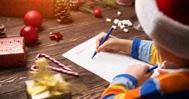 A kid writes a letter to Santa.