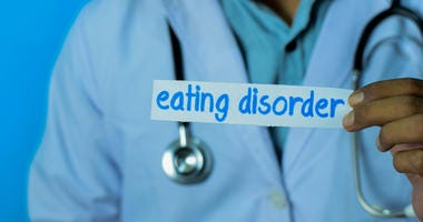 Doctor holding sign that says eating disorder.