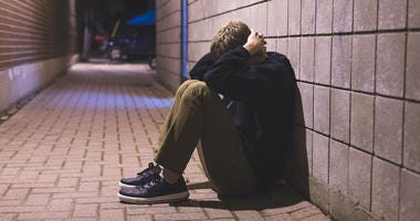 Teenager sitting in alley at night