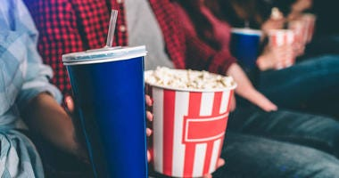 People holding popcorn and drinks in a movie theater.