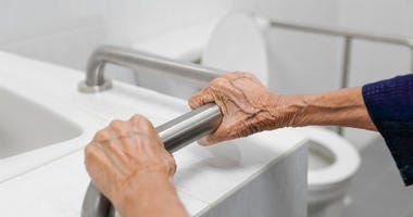 Elderly woman holding on handrail in bathroom