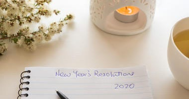 Notebook and pen with handwritten New Year's resolutions header.