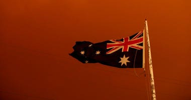 The Australia Flag flies under red skies from the fires on January 04, 2020 in Bruthen Australia.