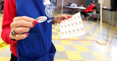 """Poll worker hands out an """"I voted"""" sticker."""
