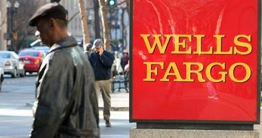 A pedestrian walks by a sign outside of a Wells Fargo bank branch.
