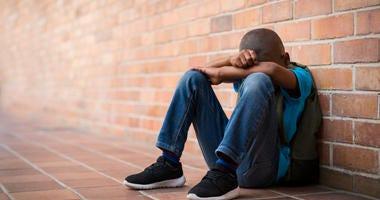 Young boy sitting alone at school.