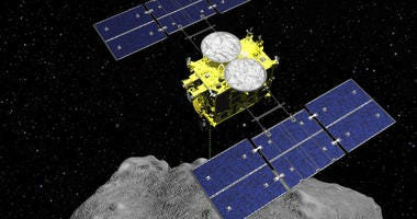 In this computer graphics image released by the Japan Aerospace Exploration Agency (JAXA), the Hayabusa2 spacecraft is seen above on the asteroid Ryugu.