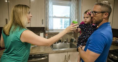 In this Aug. 1, 2018 photo, Lauren Woehr hands her 16-month-old daughter Caroline, held by her husband Dan McDowell, a cup filled with bottled water at their home in Horsham, Pa.