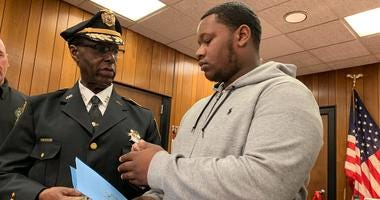 Sheriff Gilbert Wilson presents Kenney Smith with honorary coins for bravery.