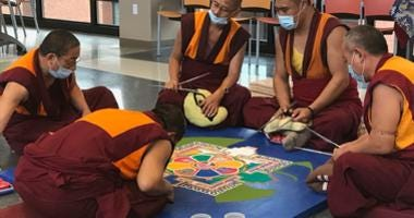 Monks tap brightly colored sand into place to form patterns and symbols