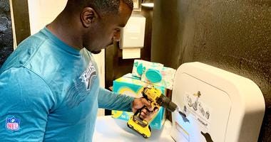 Former Eagles running back Brian Westbrook helped install a changing table in the bathroom of a barber shop in Philadelphia's Powelton Village neighborhood.