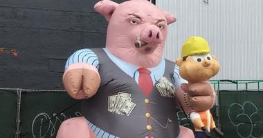 An inflatable pig has a Rolex on his wrist, pockets full of cash and a cigar in his mouth, and one of his hooves is wrapped around the neck of a construction worker.