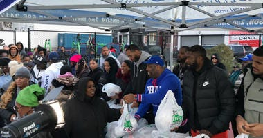Philadelphia 76ers' Tobias Harris, Mike Scott, and James Ennis III giving out turkeys in South Philadelphia.