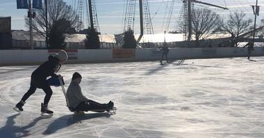 A Blue Cross RiverRink staff member pushes Dougie Peterson on a sled skate during a free adaptive ice skating event.