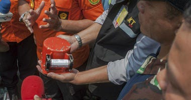 A member of National Transportation Safety Committee holds the flight data recorder from the crashed Lion Air jet.